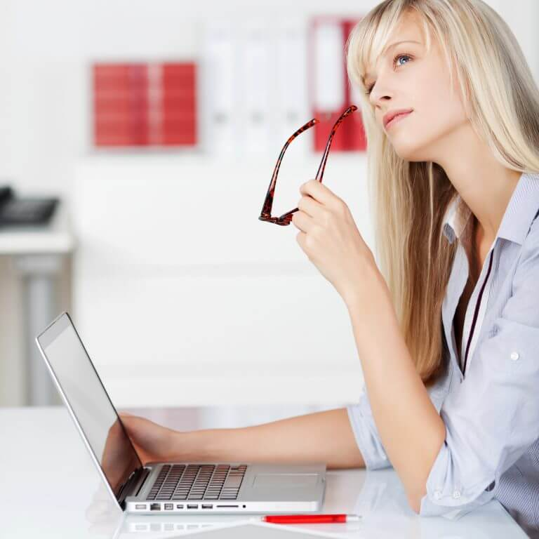 Portrait of woman looking up and thinking while holding her laptop
